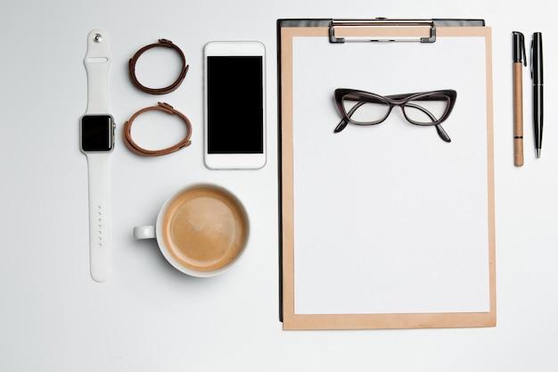 Table de bureau avec tasse, fournitures, téléphone sur une surface blanche