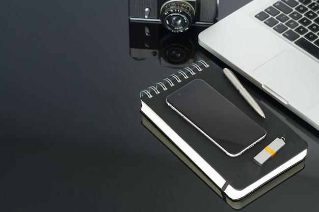 Table de bureau en verre avec ordinateur, téléphone et fournitures