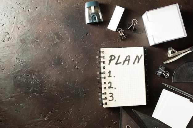 Table de bureau vue de dessus avec un bloc-notes pour planifier sur fond marron