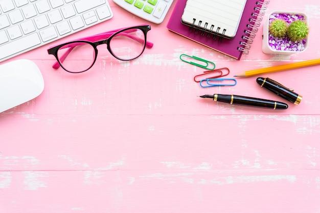 Table de bureau vue de dessus avec espace de travail et accessoires de bureau sur un fond en bois rose.