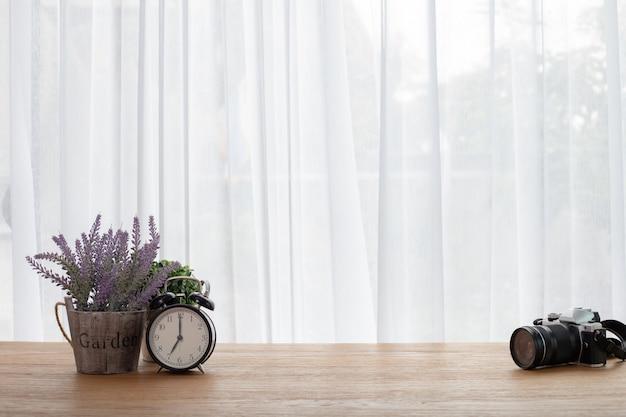 Table avec caméra, réveil rétro et belle fleur