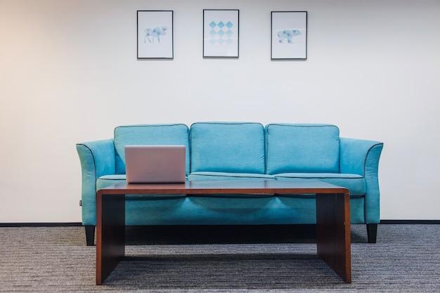 Table avec un canapé d'ordinateur portable debout dans la pièce