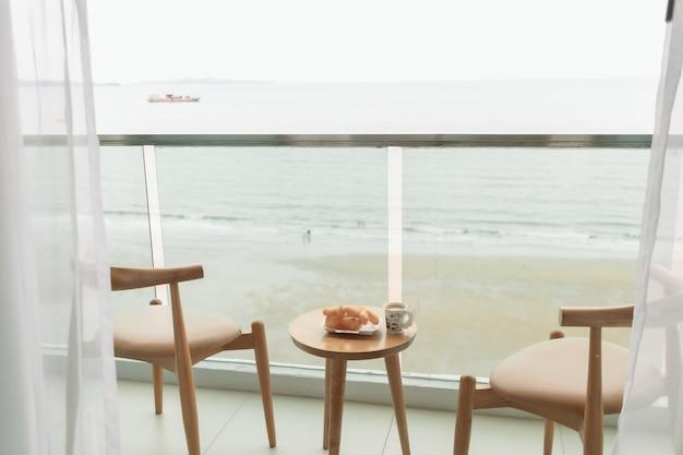 Table et chaises sur le balcon avec vue sur la mer