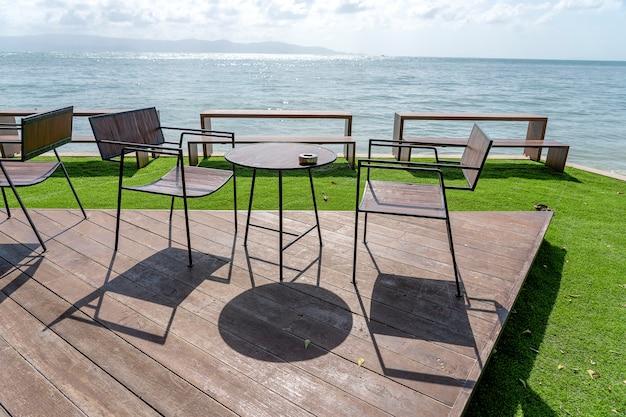 Table et chaises en bois dans un café de plage vide à côté de l'eau de mer. fermer. île de koh phangan, thaïlande