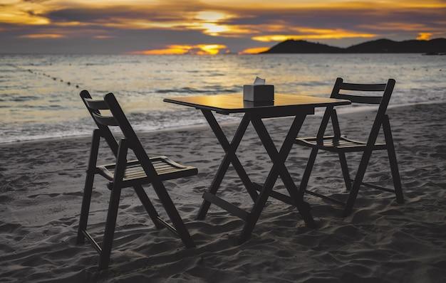 Table et chaises de restaurant sur la plage au coucher du soleil