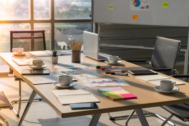 Table et chaises de réunion de plan rapproché avec la salle de conférence de tasse de café de papier d'ordinateur portable dans le bureau moderne