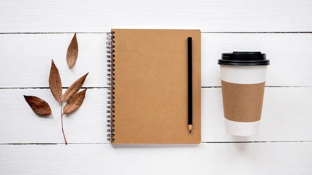 Table avec des choses de style de vie. cahier, tasse de café et une brindille séchée. vue de dessus