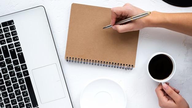 Table avec des choses de style de vie. ordinateur portable, un homme tient un stylo et une tasse de café. vue de dessus