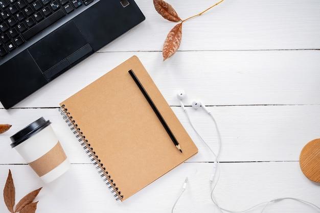 Table avec des choses de style de vie. ordinateur portable, ordinateur portable, tasse de café, écouteurs et brindilles séchées. vue de dessus