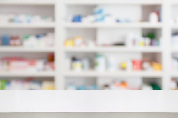 Table de comptoir de pharmacie avec fond abstrait flou avec médicaments et produits de santé sur les étagères
