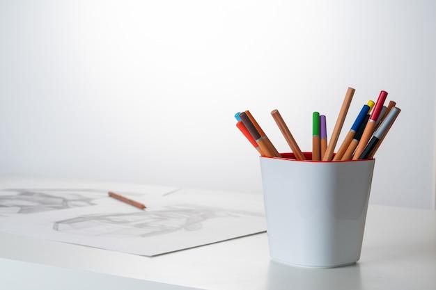 Sur la table, des crayons de couleur dessinent des feuilles avec des graphiques.