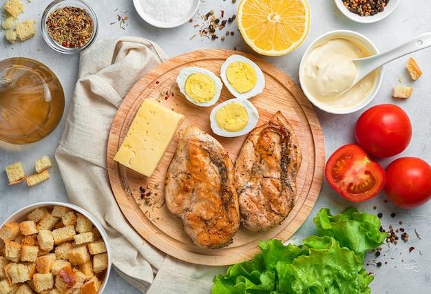 Table de cuisine avec des ingrédients pour faire la salade césar. vue de dessus. concept de cuisine.