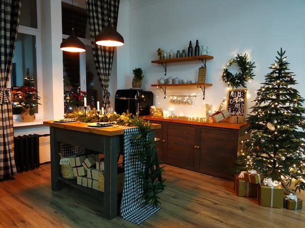 La table de cuisine de noël est décorée de branches d'arbre de noël, de bougies et de guirlandes. atmosphère chaleureuse de noël à la maison.