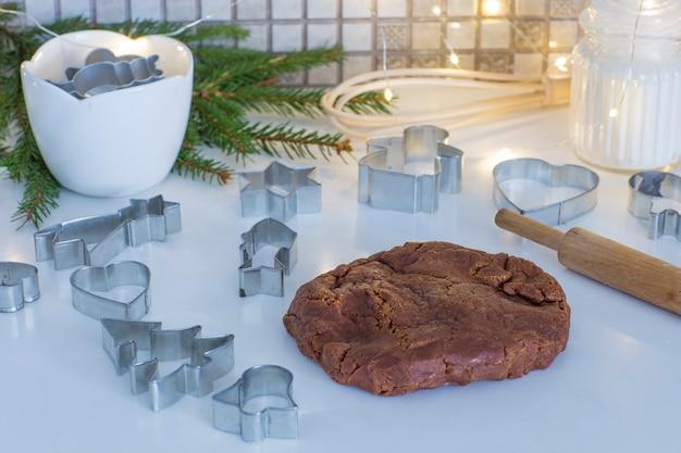 Sur la table de la cuisine pâte de gingembre, rouleau à pâtisserie, branches de sapin, farine, guirlande - préparer les vacances