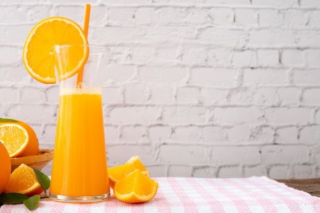 Table de cuisine avec pichet de jus d'orange sur le mur de briques blanches