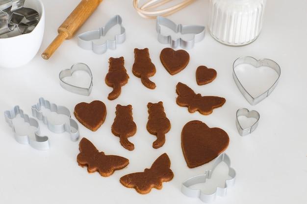 Sur la table de la cuisine sont sculptés à partir de papillons, chats, coeurs de pâte de gingembre