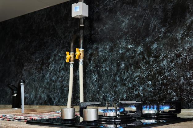 Table de cuisson domestique avec brûleurs à gaz allumés et robinet de cuisine avec eau courante