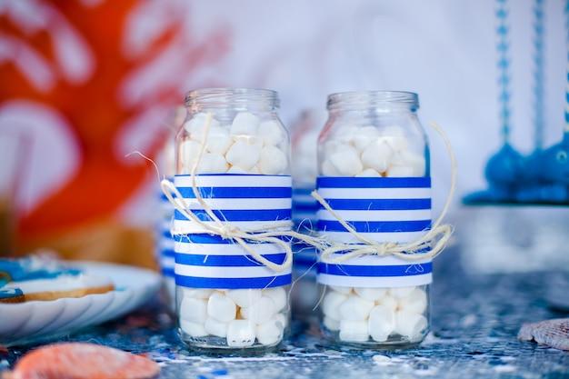 Table avec décor de mer et assiette avec des bonbons, des bonbons, des biscuits et décore des pots avec de la guimauve