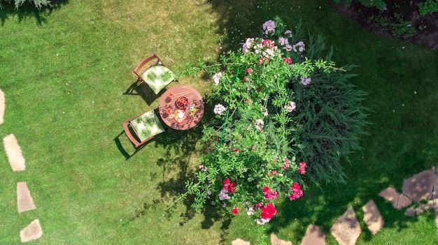 Table décorée avec des fromages, des fraises et du vin dans une belle roseraie, vue aérienne du cadre de table romantique pour deux personnes d'en haut