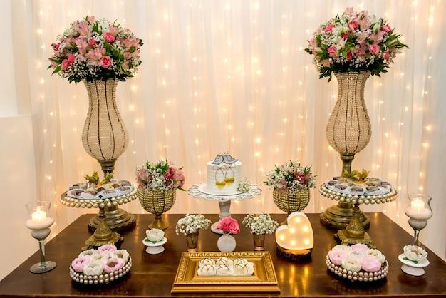 Table décorée de gâteaux, bonbons, bougies, fleurs et ornements lors d'une fête de mariage.