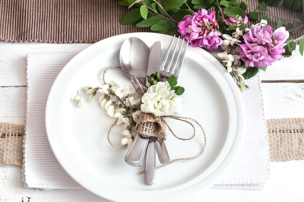Table décorée magnifiquement élégante pour des vacances avec des fleurs de printemps et des verts - mariage ou saint valentin avec des couverts modernes, un arc, un verre, une bougie et un cadeau, horizontal, gros plan, tonique