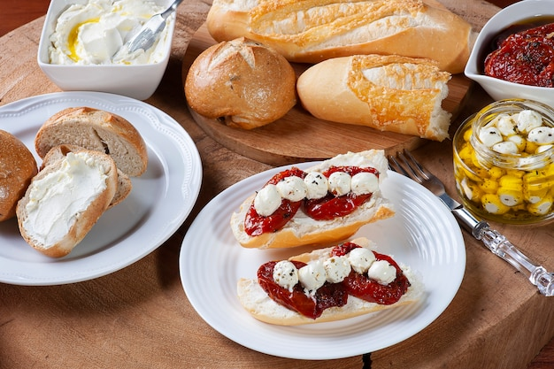 Table avec différents apéritifs. pains assortis, tomates séchées au soleil, deux types de caillé.