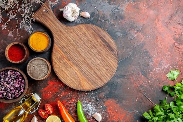 Table à dîner, bouteille d'huile tombée, planche à découper et différentes épices