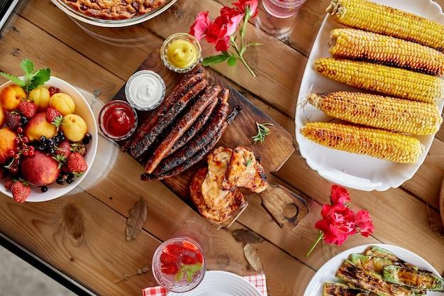 Table à dîner avec grill à viande, légumes rôtis, sauces et limonade, variété d'apéritifs servant sur une table de fête en plein air.
