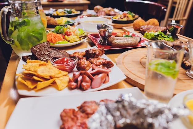 Table à dîner avec grill à la viande, pommes de terre nouvelles rôties, légumes, salades, sauces, collations et limonade, vue de dessus.