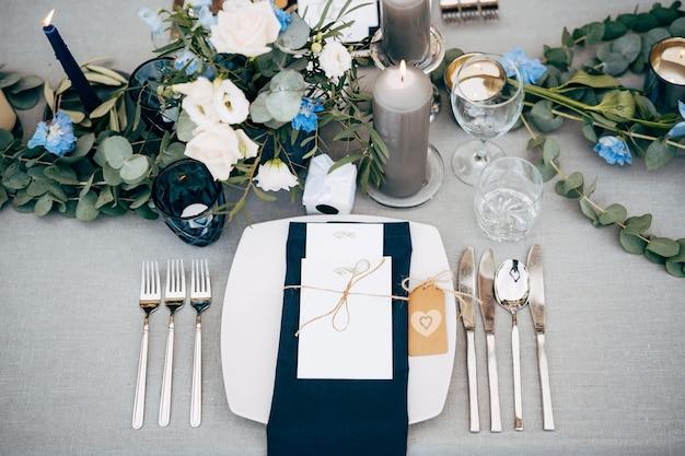 Table de dîner de mariage réception d'une assiette carrée avec une serviette en tissu bleu couteaux et fourchettes à côté de la