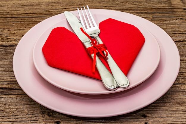 Table de dîner romantique avec assiettes et serviette en forme de coeur