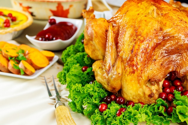 Table de dîner de thanksgiving avec dinde rôtie avec sauce aux canneberges et igname.