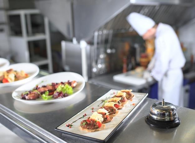 La table de distribution dans la cuisine du restaurant. le chef prépare un repas sur le fond des plats finis.