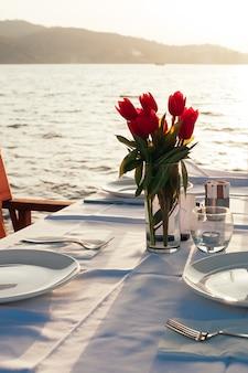 Table dressée avec des fleurs au restaurant de la plage