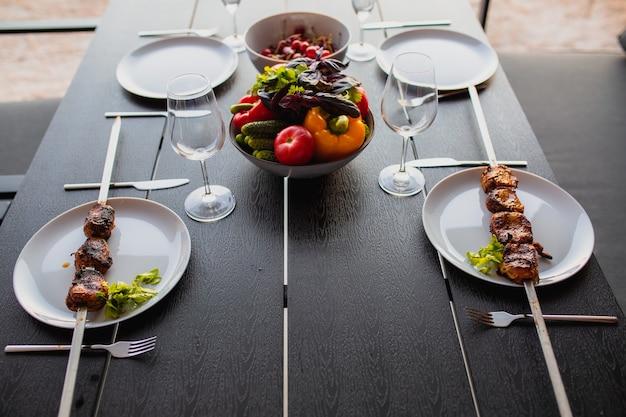 Table dressée pour quatre sur la terrasse d'ététerrasse d'été entre amisdîner sur la terrasseensemble de table