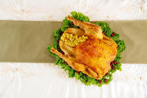 Table du dîner de thanksgiving servie avec de la dinde, décorée de chou frisé et de canneberge.