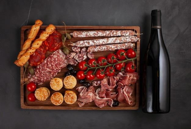 Table d'entrées avec différents antipasti, fromages, charcuterie, snacks et vin.