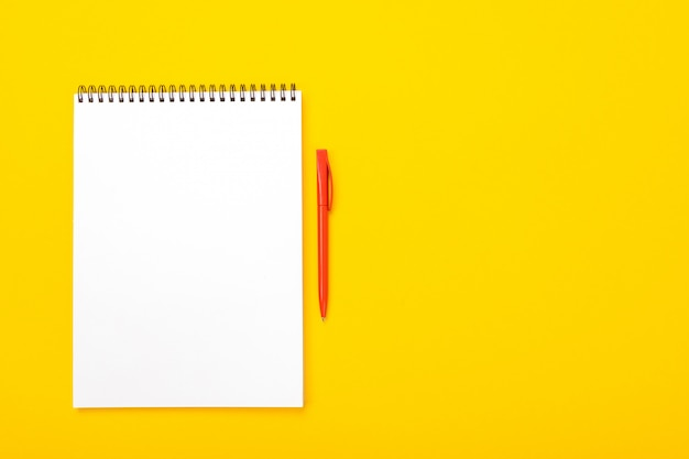Table de l'espace de travail avec carnet et stylo avec fond isolé sur fond jaune