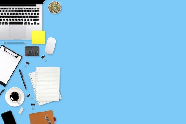 Table d'espace de travail à plat avec ordinateur portable, fournitures de bureau, tasse à café, tablette et téléphone portable sur fond bleu pastel