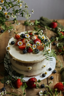 Sur la table est un gâteau décoré de baies et de fleurs