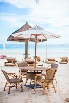 Table d'été vide en plein air sur la plage au coucher du soleil