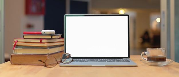 Table d'étude avec pile de livres, maquette d'ordinateur portable, smartphone, verres et tasse à café sur table en bois