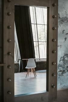 Une table ou un fauteuil blanc se reflète dans un grand miroir de sol en studio.