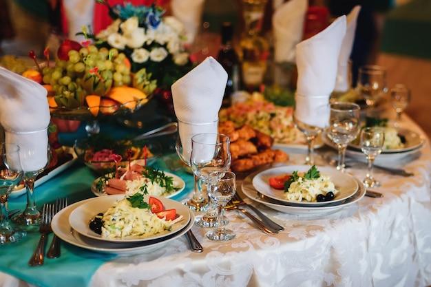 Table de fête au restaurant avec assiettes, verres et couverts sur une nappe blanche