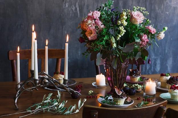 Table de fête avec bouquet de fleurs, bougies et cupcakes
