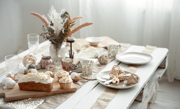 Une table de fête avec un cadre magnifique, des détails décoratifs, des œufs et un gâteau de pâques