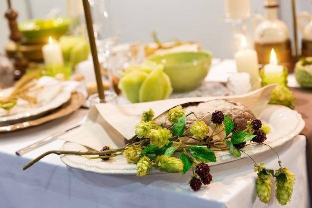 Table de fête décorée de bougies et de fleurs gros plan, personne. célébration de vacances