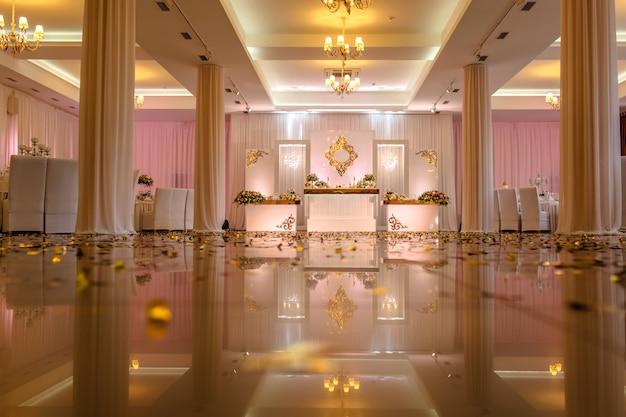 Table de fête décorée de composition de fleurs blanches, rouges et roses et de verdure dans la salle de banquet.