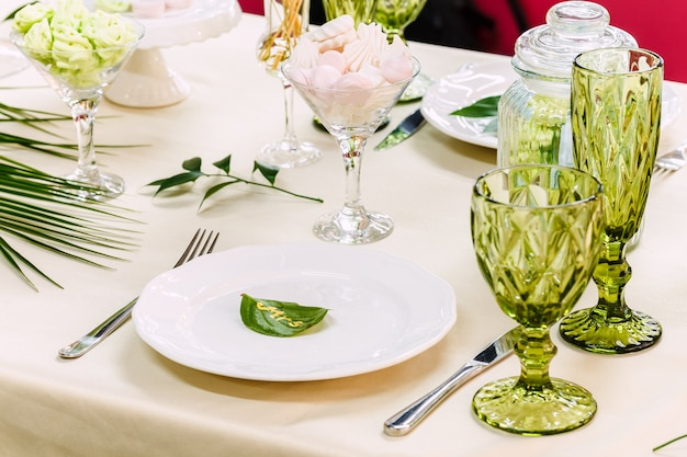 Table de fête, décorée de vases, fruits et pâtisseries. dans la décoration de la table utilisé des éléments de fleuristerie.
