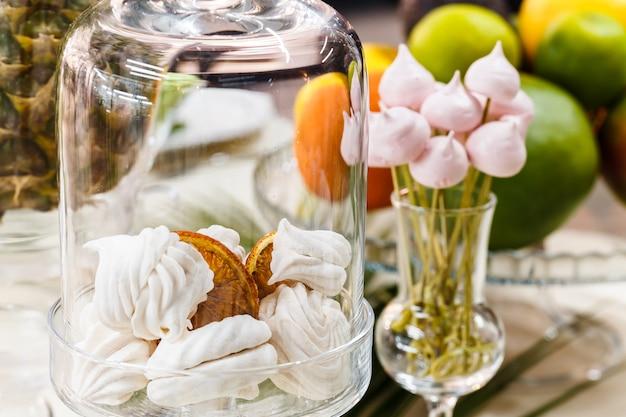 Table de fête décorée de vases, fruits et pâtisseries.